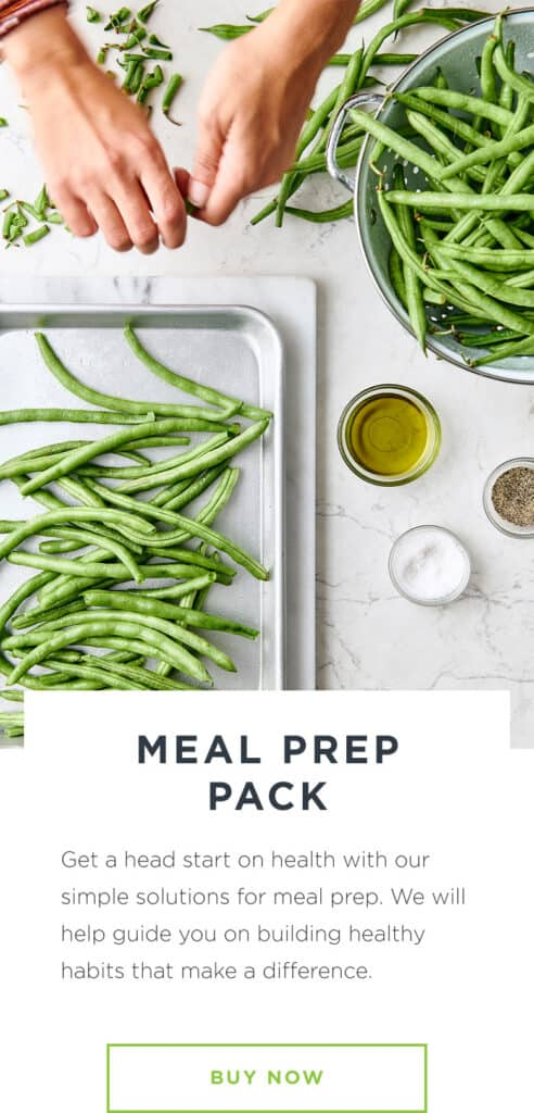 Woman meal preps green beans for roasting on a sheet pan next to a bowl of beans on white marble